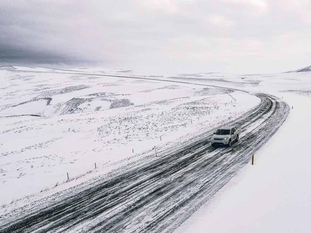 Autó halad a jeges, havas utakon a havas tájban januárban izlandon.